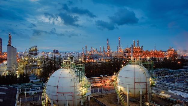 Gasspeicherkugeltanks und pipeline in der industrieanlage der öl- und gasraffinerie mit glitzer-beleuchtungsindustrie in der dämmerung