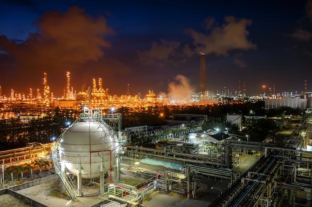 Gasspeicherkugeltanks und -pipeline in der industrieanlage der öl- und gasraffinerie mit glitzerbeleuchtungsindustrie bei nacht
