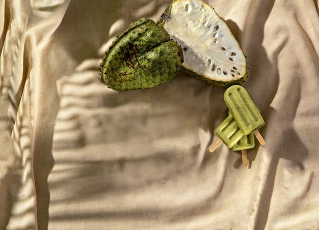 Gaviola-eis am stiel mit gaviola-frucht auf einem stoffsockel, sonnenlicht, draufsicht. platz kopieren