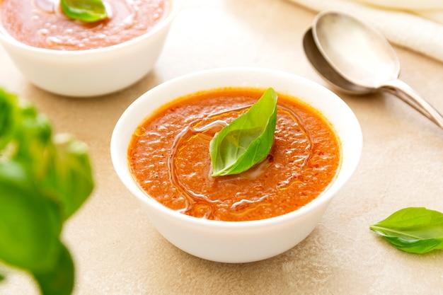 Gazpacho kalte tomatensuppe mit basilikum und zwei löffeln auf hellem hintergrund
