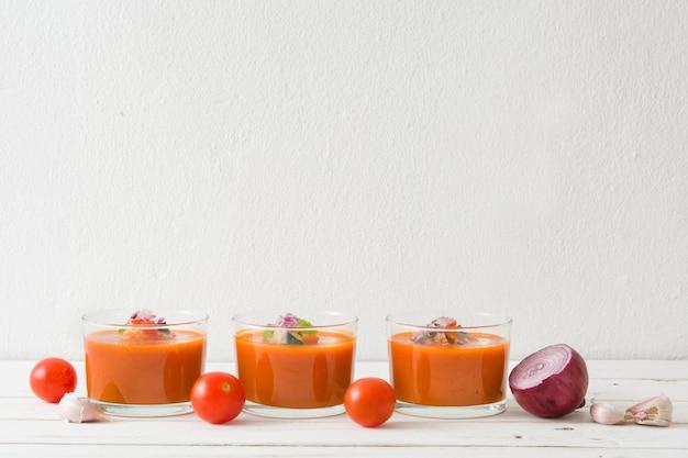 Gazpacho-suppe in gläsern auf weißem holztisch