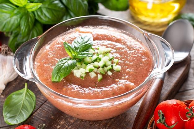 Gazpacho-suppe. traditionelle spanische kalte tomatensuppe aus frischem rohem gemüse mit kochzutaten auf einem holztisch