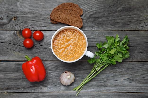 Gazpacho-suppe und zutaten auf dunkler holzoberfläche