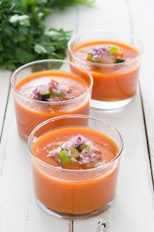 Gazpacho-suppe und zutaten auf weißem holz