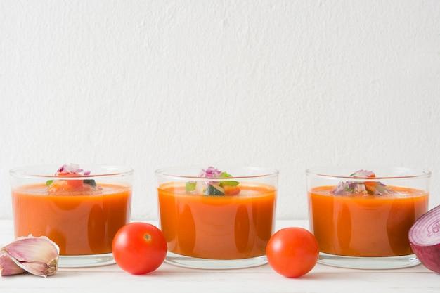 Gazpacho-suppe und zutaten auf weißem holztisch