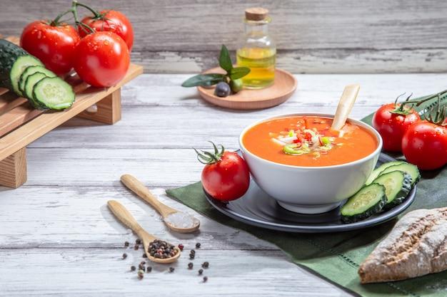 Gazpacho. traditionelle spanische tomatensuppe mit frischen tomaten, frischer gurke und olivenöl, auf weißem holzsockel