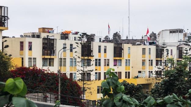 Gealterte fassade des modernen mehrstöckigen farbigen wohngebäudes im historischen zentrum von lima peru, gelbe und orange wände, bäume