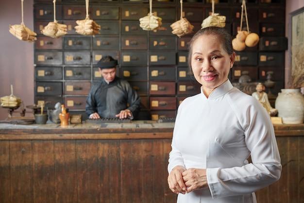 Gealterte frau an der traditionellen asiatischen apotheke