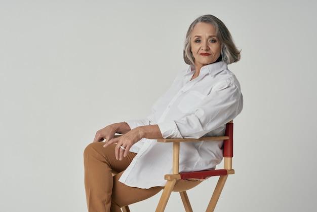Gealterte frau im weißen hemd sitzt auf einem stuhl rote lippen isolierten hintergrund. foto in hoher qualität