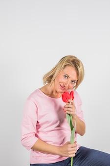 Gealterte frau in rosafarbener bluse mit blume