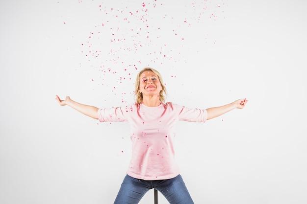 Gealterte glückliche dame in der rosafarbenen bluse mit den händen zu den seiten zwischen konfetti