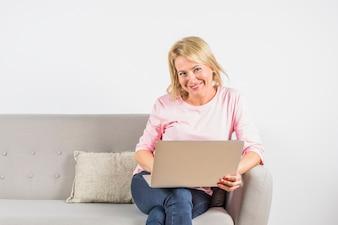 Gealterte lächelnde Frau in der rosafarbenen Bluse mit Laptop auf Sofa