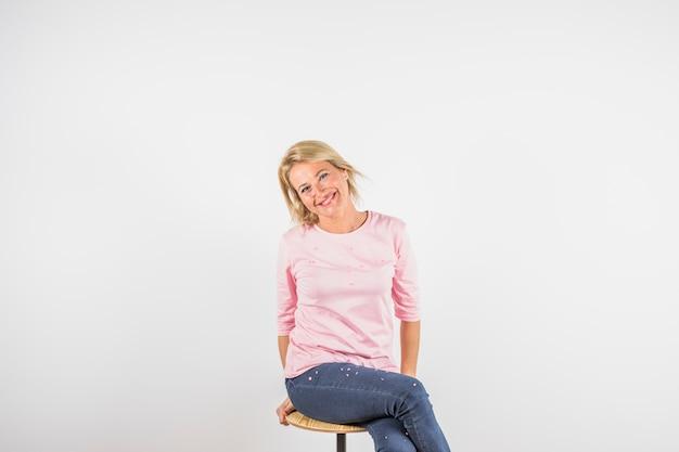 Gealterte lächelnde frau in rosafarbener bluse auf schemel