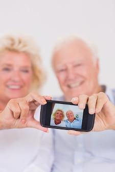 Gealterte paare, die fotos mit smartphone machen