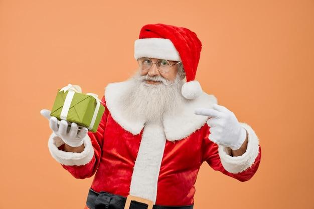Gealterte santa claus, die kamera betrachtet und auf geschenkbox zeigt
