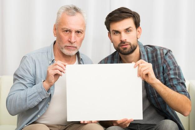 Gealterter ernster mann und junger kerl, die papier auf sofa hält