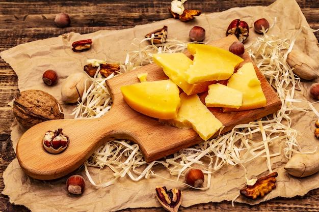 Gealterter gouda-käse mit pekannuss-walnüssen und haselnüssen auf altem holztisch