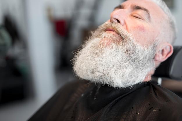 Gealterter grauer behaarter mann, der im salon sich entspannt