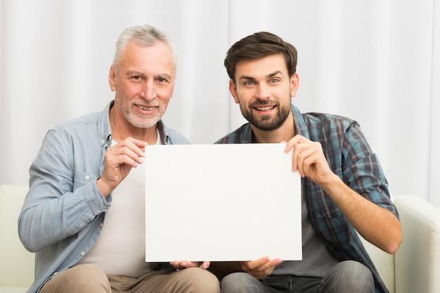 Gealterter lächelnder mann und junger glücklicher kerl, der papier auf sofa hält