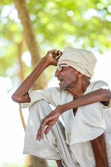 Gealterter ländlicher indischer mann, der auf dem boden sitzt