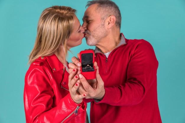 Gealterter mann, der mit frau küsst und schmuckkasten zeigt