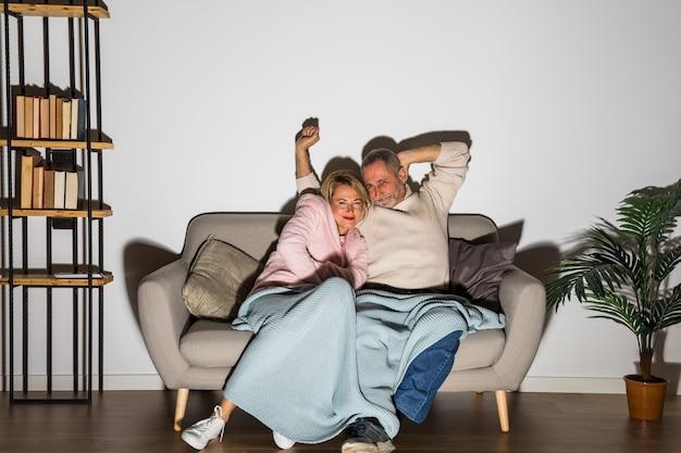 Gealterter mann mit den angehobenen händen nahe der lächelnden frau, die auf sofa fernsieht