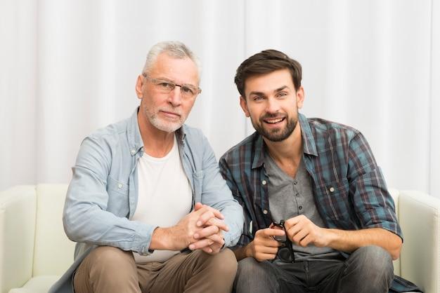Gealterter mann und junger glücklicher kerl, die hände auf sofa umklammert