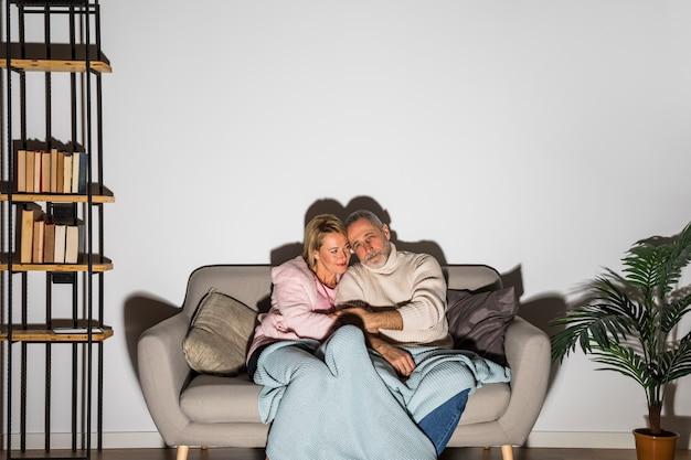 Gealterter mannhändchenhalten mit frau und auf sofa fernsehen
