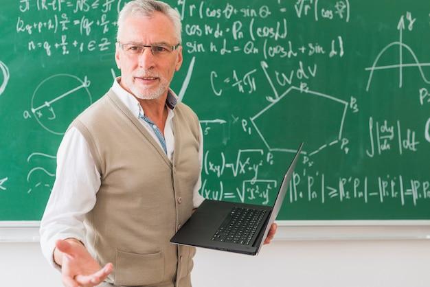 Gealterter mathelehrer, der mit notizbuch steht