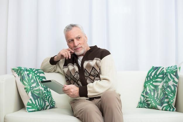 Gealterter nachdenklicher mann, der tablette auf sofa verwendet