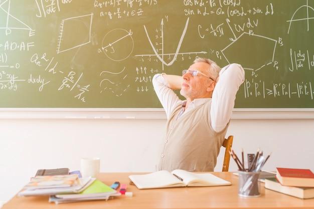 Gealterter professor, der im klassenzimmer sich entspannt