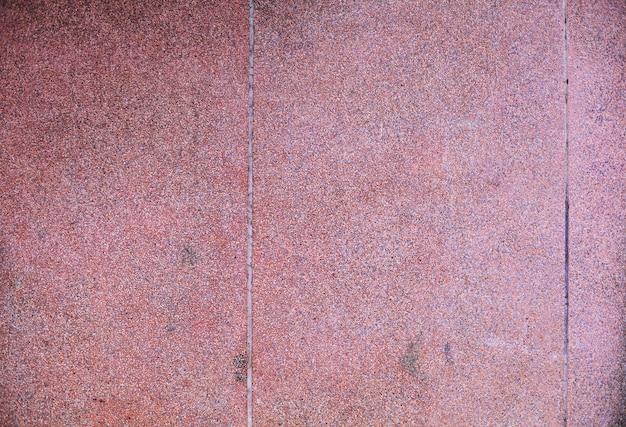 Gealterter traditionelles asiatisches tropisches rot der nahaufnahme färbte groben strukturierten konkreten steinwandhintergrund des schmutzes des gebäudes