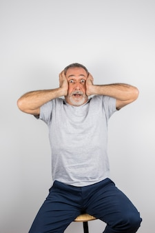 Gealterter überraschter Mann mit den Händen auf Kopf auf Stuhl