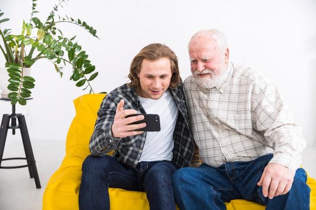Gealterter vater, der smartphone mit jungem sohn grast