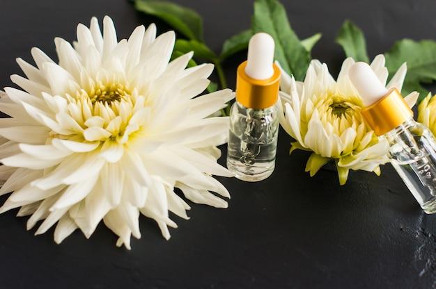 Gealuronsäure in kosmetikflaschen vor dem hintergrund weißer dahlie. intensive feuchtigkeitspflege, pflege und erhaltung der jugendlichen haut.