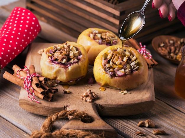 Gebackene äpfel gefüllt mit beeren, walnüssen und honig auf einem hölzernen schneidebrett.