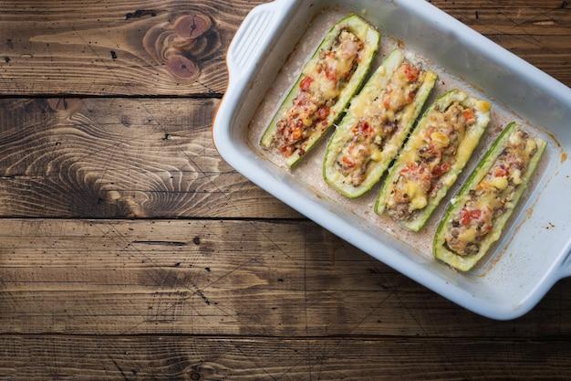 Gebackene angefüllte zucchiniboote mit gehackten hühnerpilzen und gemüse mit käse auf einem backblech. draufsicht copyspace