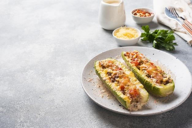Gebackene angefüllte zucchiniboote mit gehackten hühnerpilzen und gemüse mit käse auf einer platte. copyspace