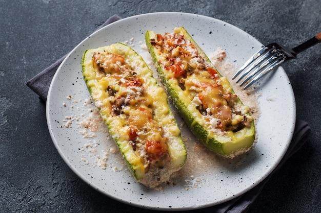 Gebackene angefüllte zucchiniboote mit gehackten hühnerpilzen und gemüse mit käse auf einer platte.