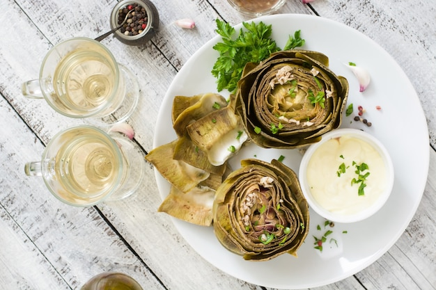 Gebackene artischocken gekocht mit knoblauchsauce, senf und petersilie. draufsicht