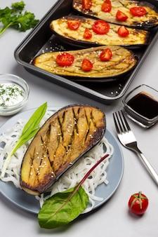 Gebackene aubergine mit gemüse und reisnudeln auf teller. gebackene aubergine mit tomaten in palette. sauce in glasschüssel. draufsicht