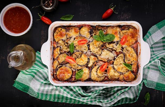 Gebackene aubergine mit käse auf einem dunklen holztisch. parmigiana melanzane. ansicht von oben. italienische küche.