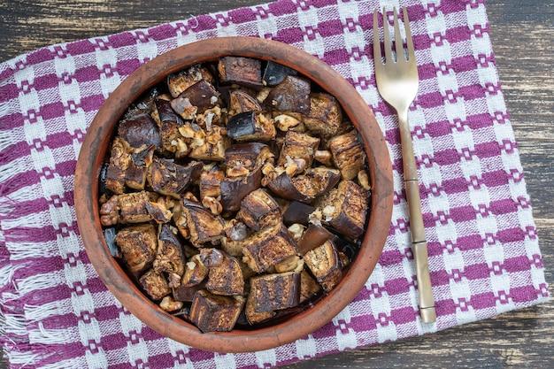 Gebackene aubergine mit walnuss, olivenöl und gewürzen auf einem teller auf dem holztisch. vegetarisches essen. nahaufnahme, ansicht von oben