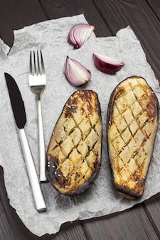 Gebackene aubergine mit zwiebelmesser und gabel auf papier