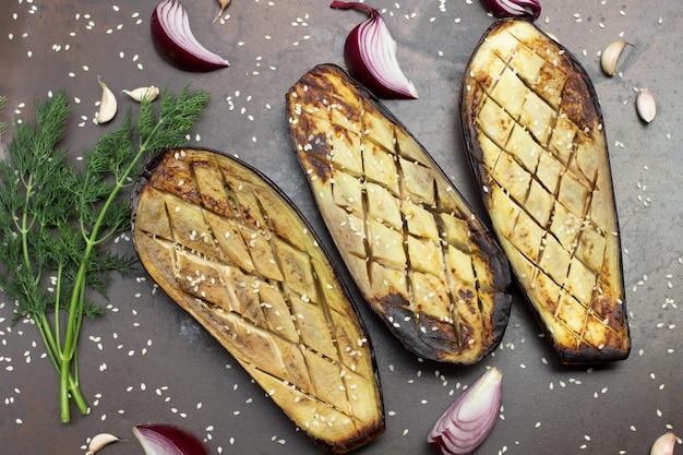 Gebackene aubergine mit zwiebeln knoblauch und sesam dillzweig