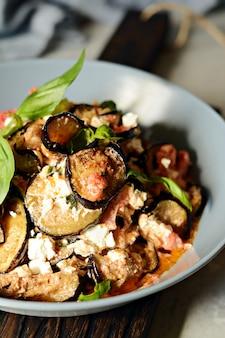 Gebackene auberginen mit tomaten, zwiebeln und feta. gemüsebeilage.