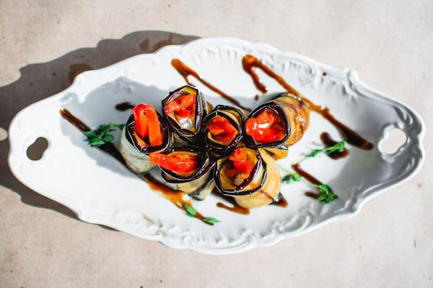 Gebackene auberginenröllchen mit hühnerzwiebeln und karotten in einem teller closeup