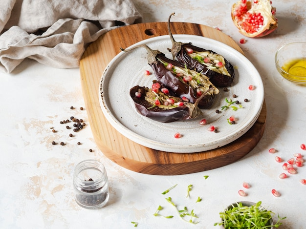 Gebackene auberginenscheiben mit gewürzen, sprösslingen, granatapfel und olivenöl auf einer weißen keramischen platte auf einem grau.