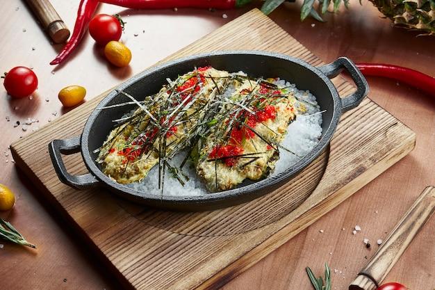 Gebackene austern mit cheesy gratin topping, nori und rotem tobiko-kaviar auf heißem salz in einer schwarzen pfanne in einer komposition mit zutaten auf einer holzoberfläche