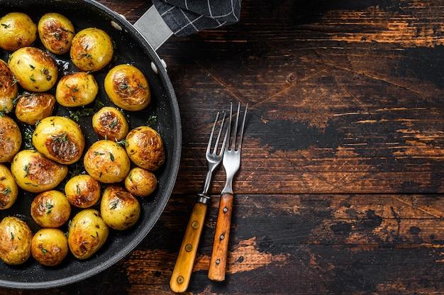 Gebackene babykartoffeln in einer gusseisernen pfanne.